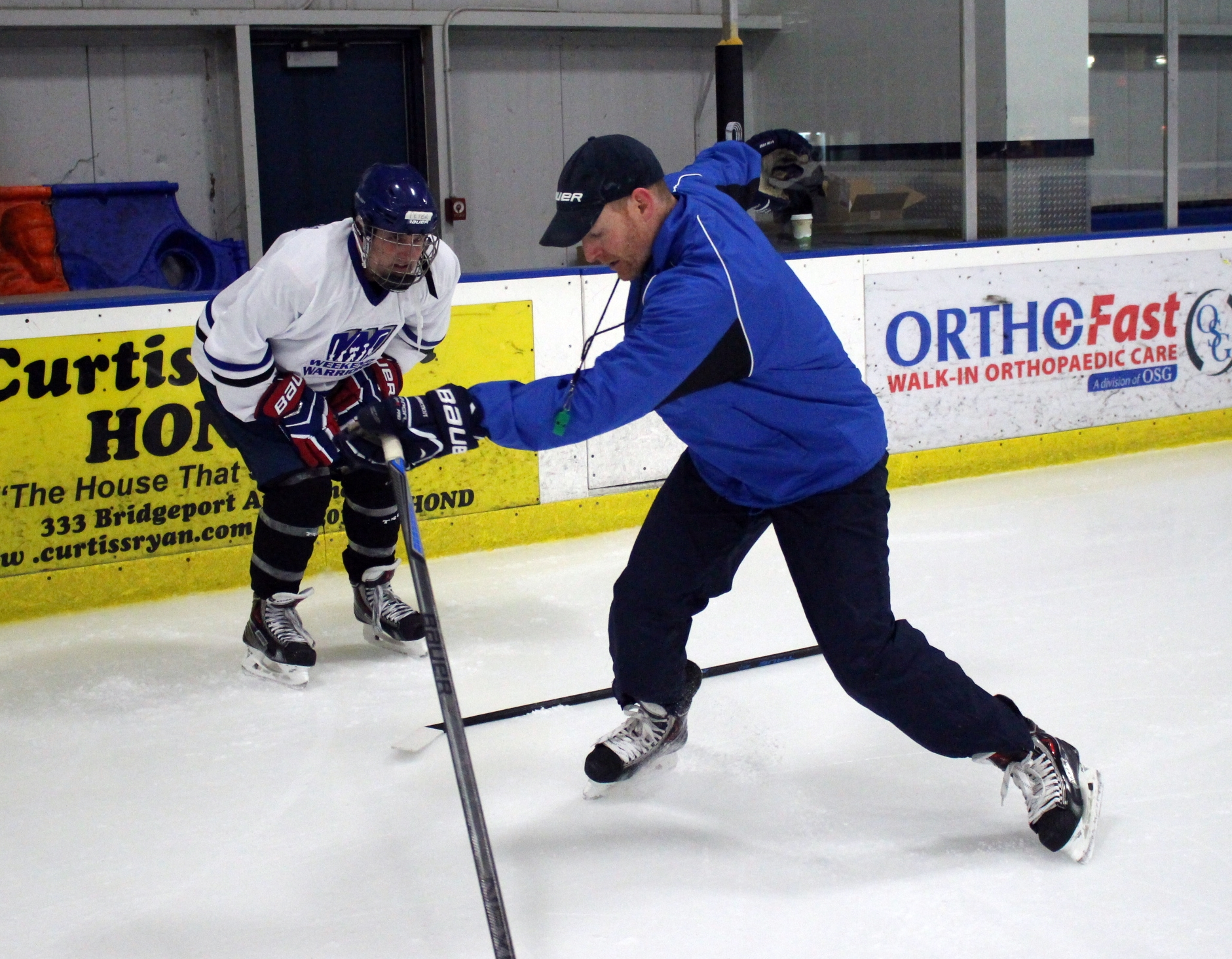 Coach Casey helps a player with his skating stride