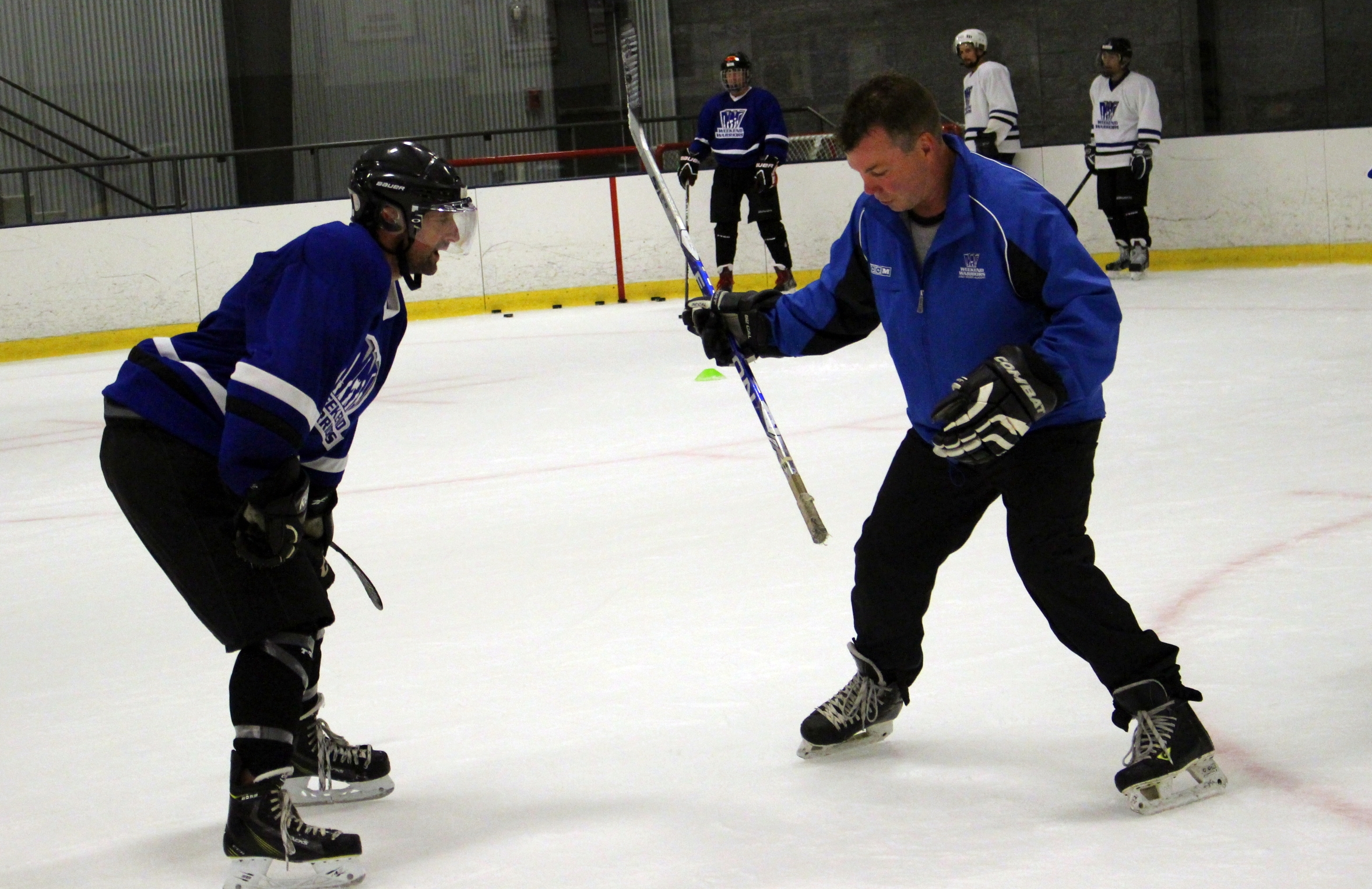 Coach Kevin helps player with wrist shot